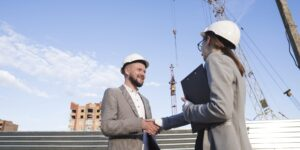 smiling-engineers-shaking-hands-at-construction-site-for-architectural-project